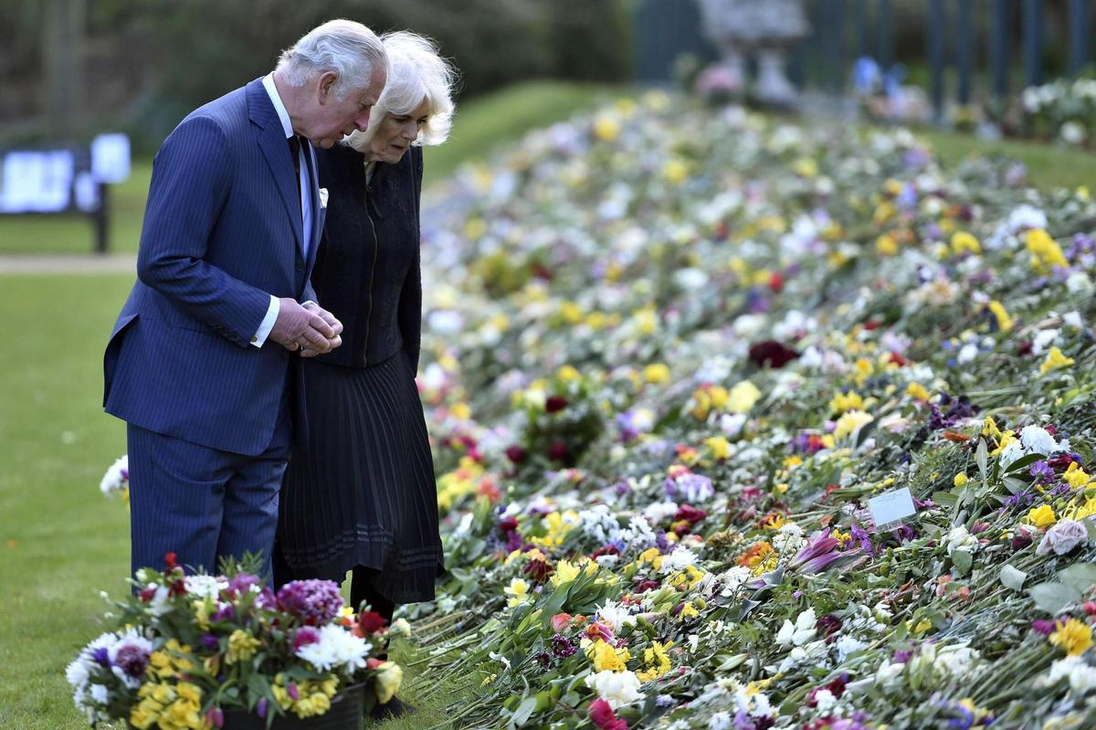 The heir to the throne, Prince Charles and Camilla, Duchess of Cornwall, look at the flowers and messages people left after Prince Philip's death.