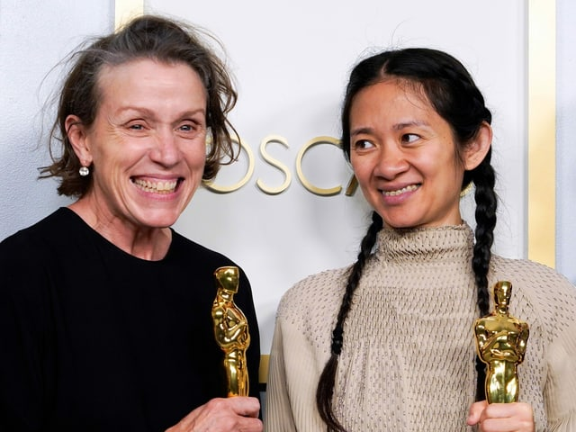 Two women each hold an Oscar