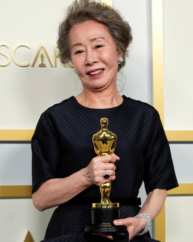 An elderly woman holds an Oscar statue in her hands