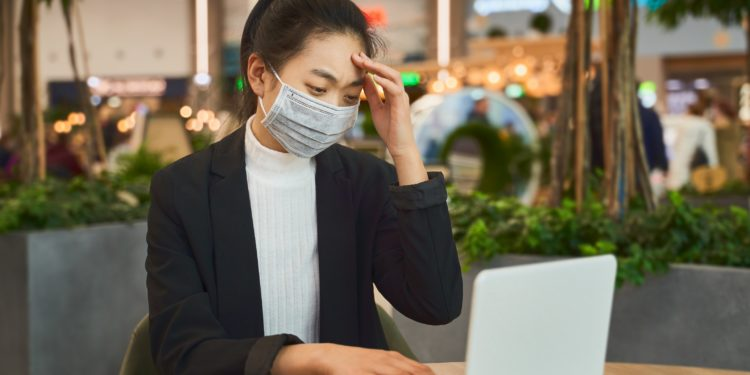 A woman sits with a face mask in front of a notebook.