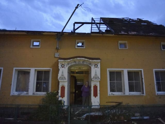 Woman in front of a building with a collapsed roof
