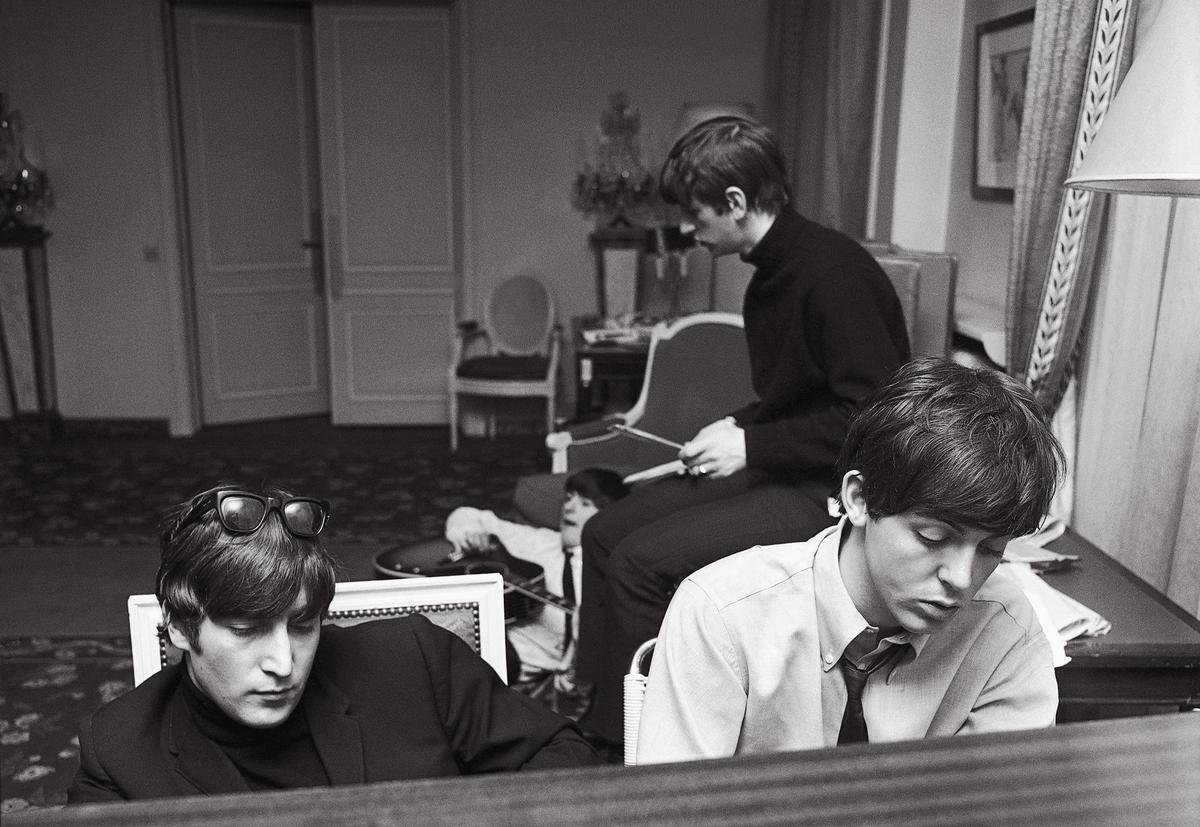 John Lennon (left) and Paul McCartney composing at the George V Hotel in Paris.  Guitarist George Harrison and drummer Ringo Starr can be seen in the background.  (January 1964)