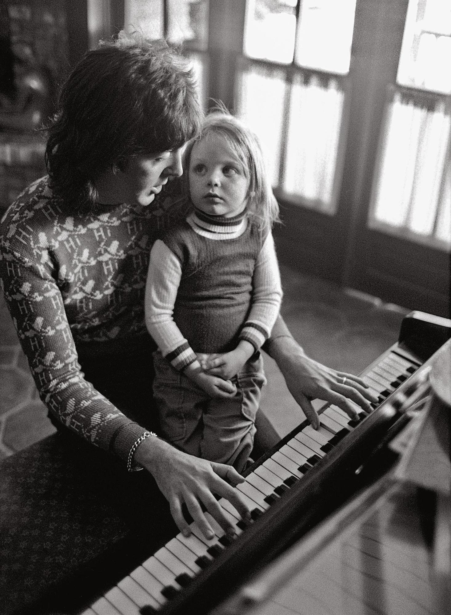 Three-year-old Stella listens to her father composing music.  (Los Angeles, March 1975)