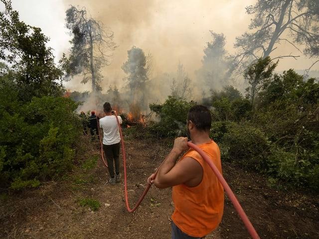 Men holding a fire hose.  Firefighters on the edge of Khartoum.