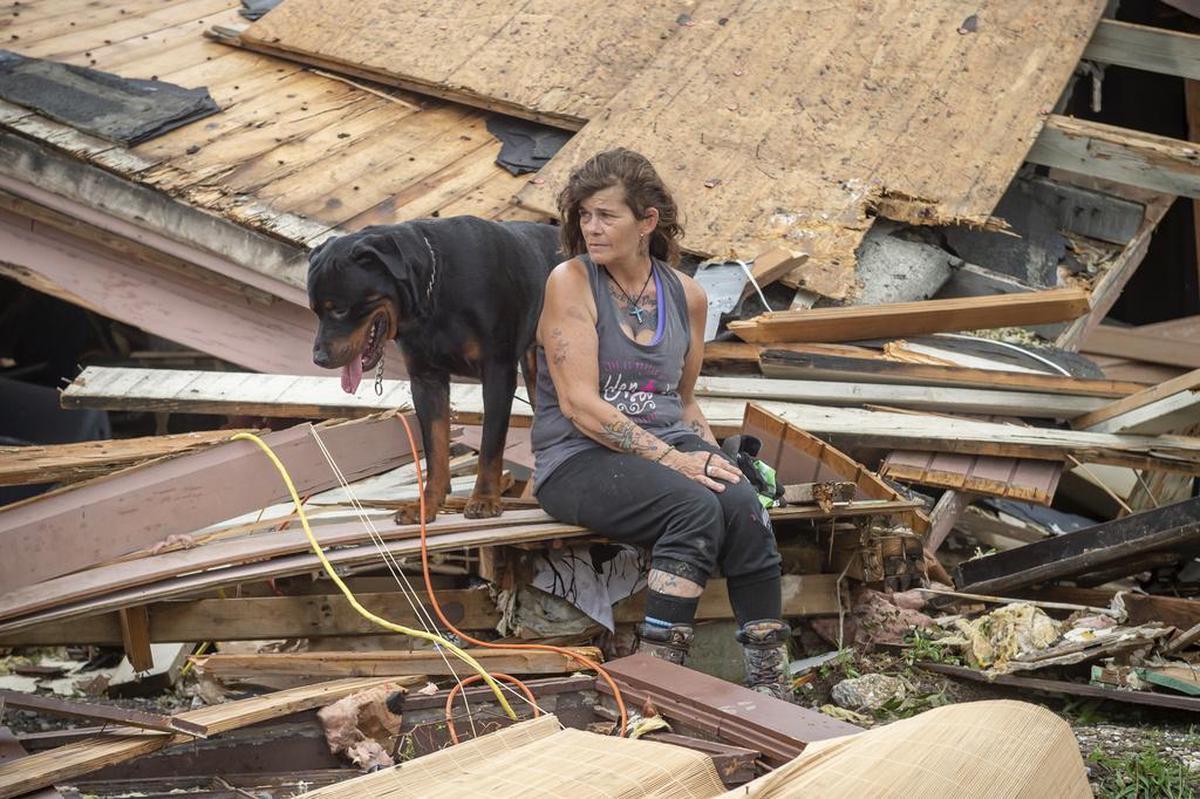 A woman and her dog sit in front of their home destroyed by Hurricane Ida in Homa, Luciana.