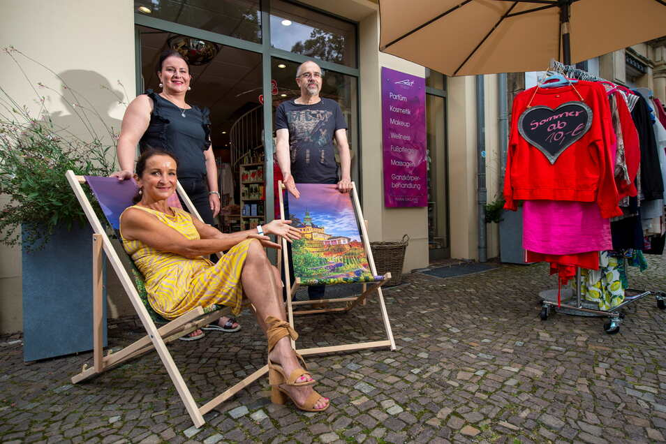 Gudrun and Pia Ast of the perfume and fashion store of the same name and Peter Pforch of Janny's Eis (left to right) invite customers to relax in the lounge chairs in front of their stores on Bahnhofstrasse.