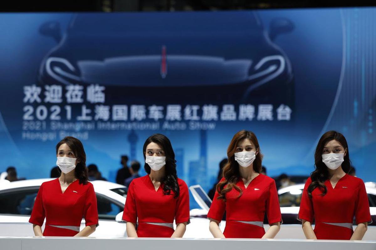Wealthy Chinese customers suddenly risk losing out to Swiss banks: receptionists from a luxury car brand wait for visitors at a Shanghai auto show.