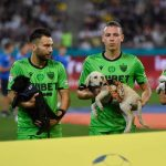 Romanian football players run to the field with dogs